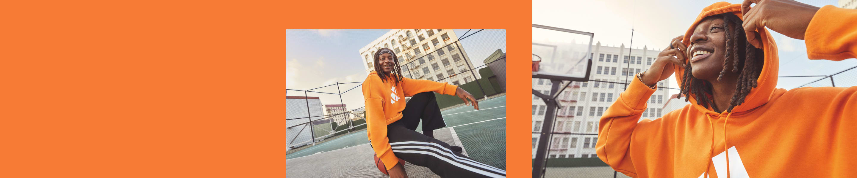 A woman sits on a basketball court, her back to the camera. She wears a orange adidas hoody and black adidas bottoms.