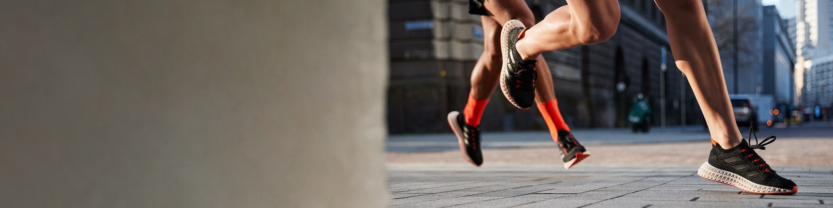 Close-up of two people wearing the new 4DFWD running shoe while running on a city street.