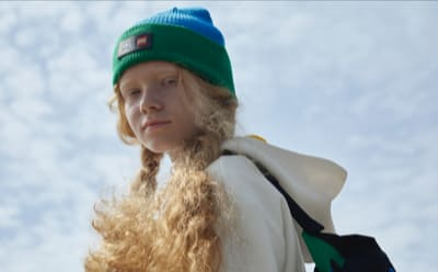 A model sporting a green and blue beanie from the adidas x LEGO® week collection.