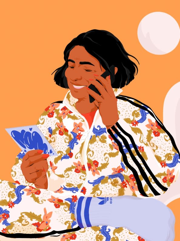 Mom talks to her daughter with her Mother's Day card in hand wearing a new floral track top.