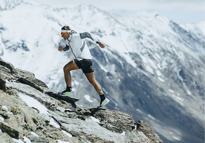 Athlete Dima wearing the Agravic Ultra running up rocky mountain trails