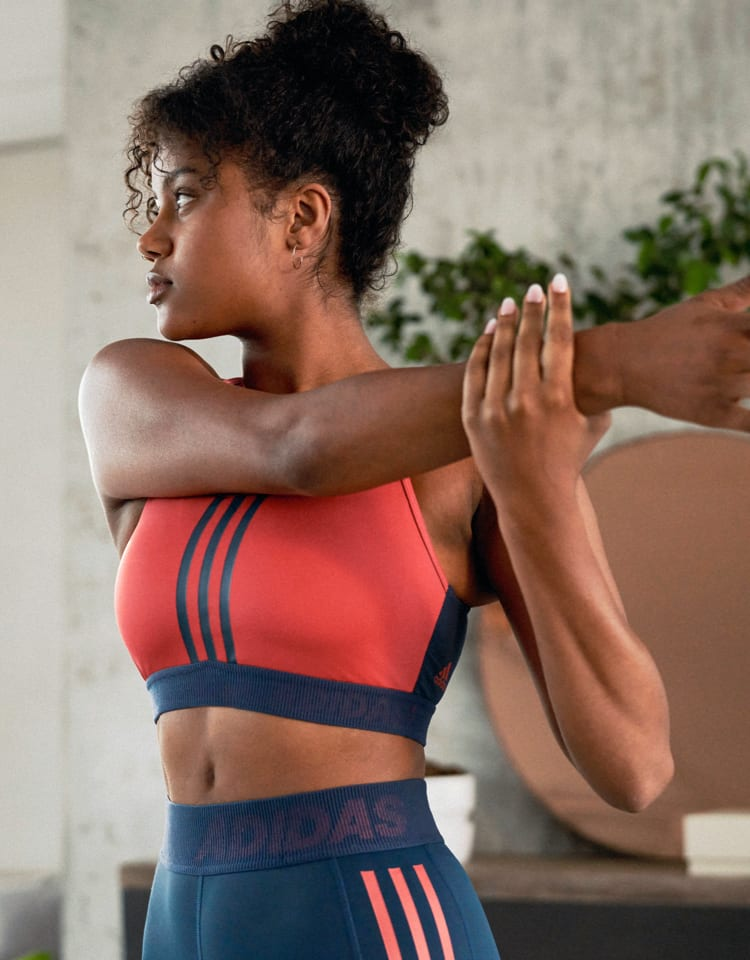 A woman wearing a red adidas bra looks over her shoulder as she stretches her arm.