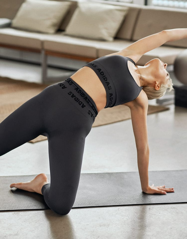 A woman in a black bra and tights stretches in a yoga pose on a mat.