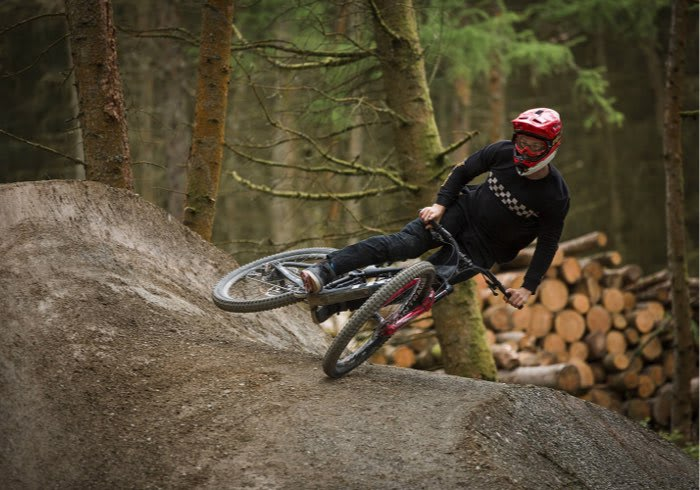 A man riding a bike in the forest.