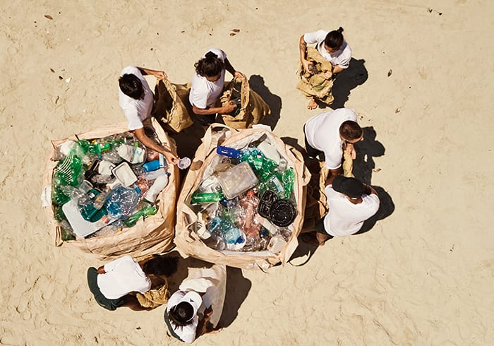 There are people on the beach, surrounding bags filled with plastic waste