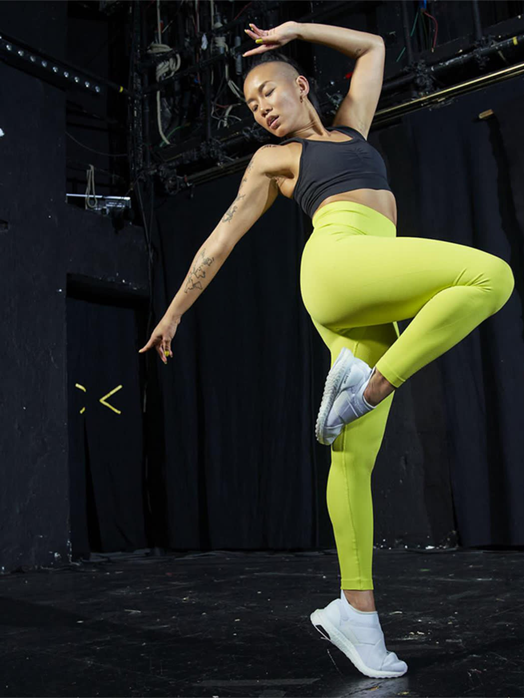 Image showing a woman in bright yellow leggings from Adidas Formotion making a jump with one knee raised high