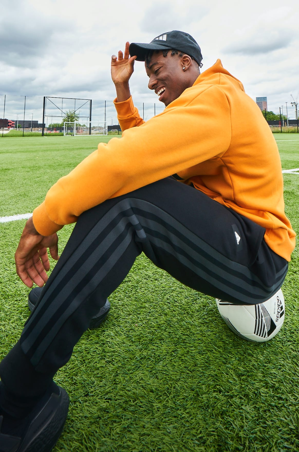 English football player Noni Madueke sits on a football pitch in adidas clothing, smiling as he adjusts his cap.
