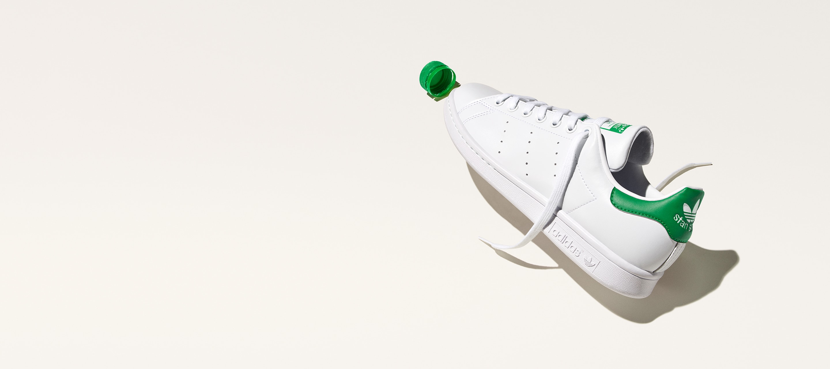 Stan Smith shoes stand upright. A plastic bottle cap leans against one. The years 1973 and 2021 are typed beside the shoes.
