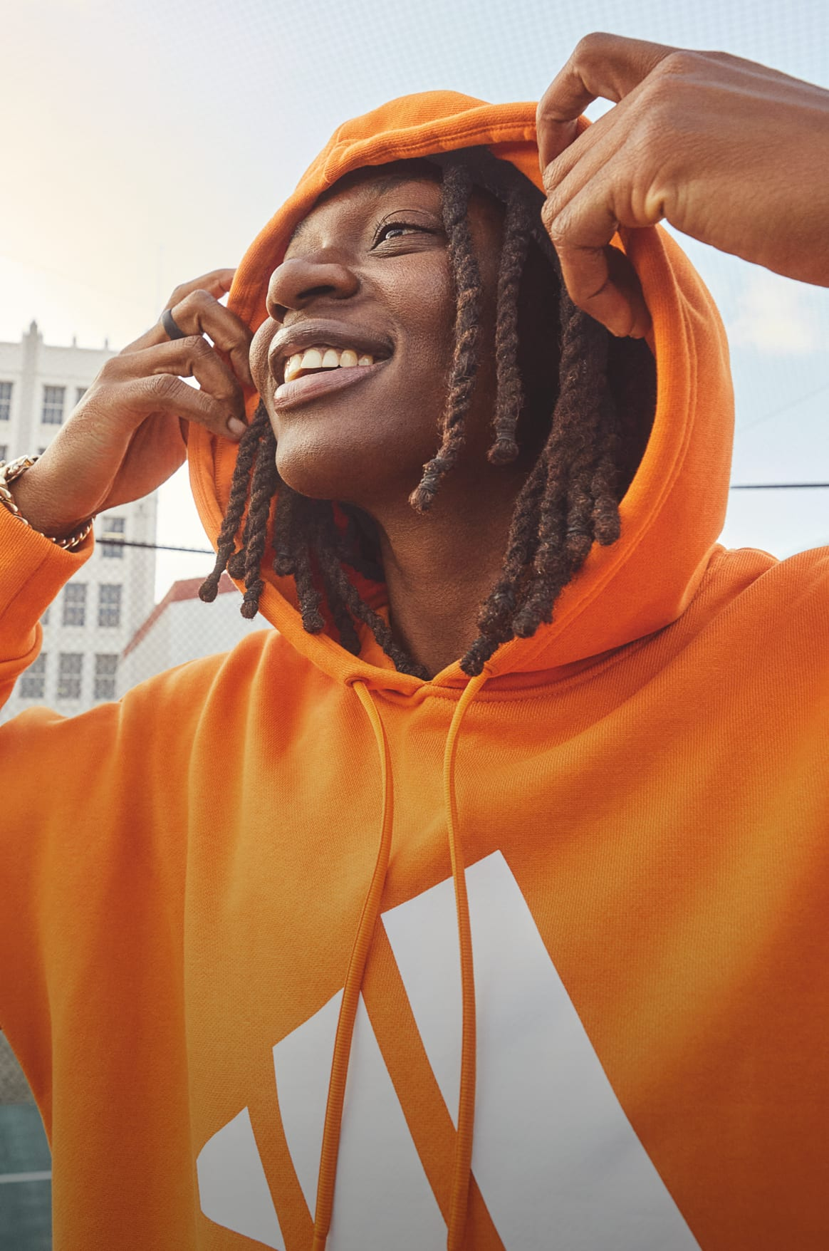 WNBA star Erica Wheeler smiles as she pulls her orange adidas hoody away from her face.