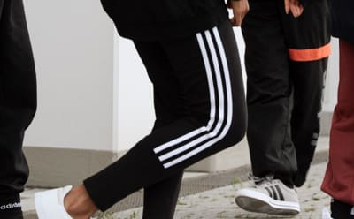A close-up of a group of people's legs, all wearing adidas pants.