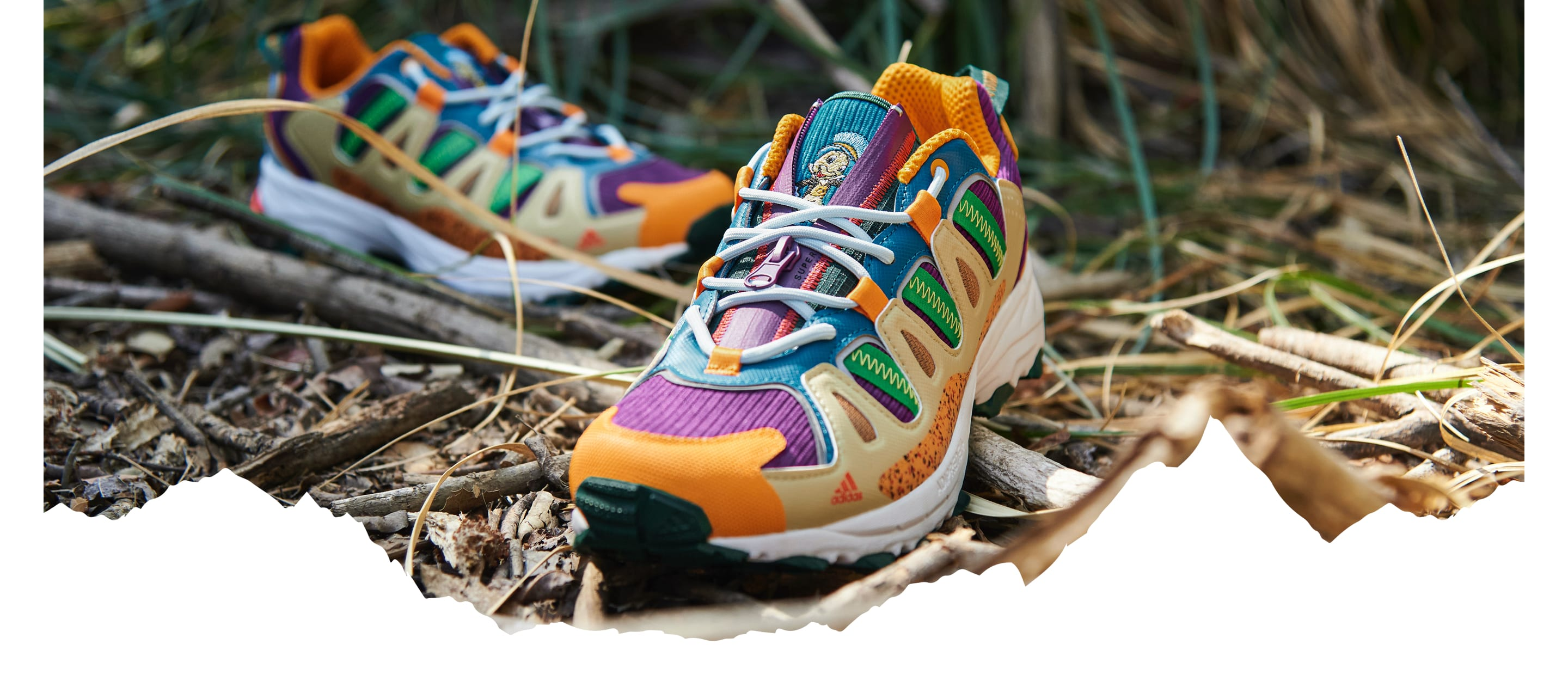 A pair of colourful Superturf Adventure sneakers on the ground, covered with sticks, branches and grass.