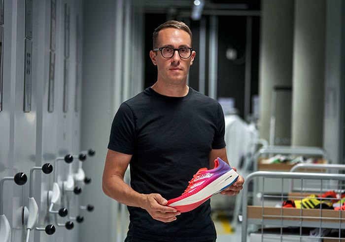 adidas design VP holding an ADIZERO running shoe
