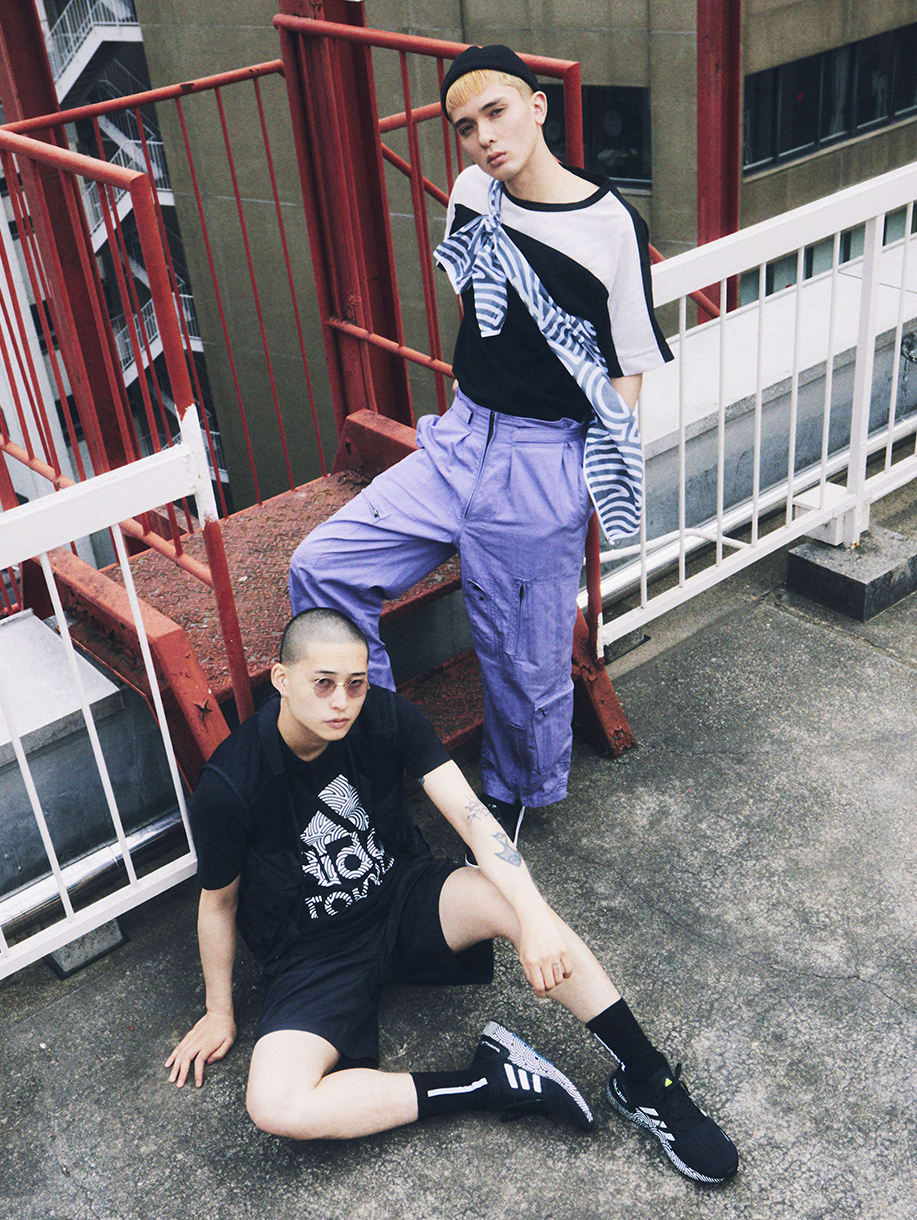 Two young men wearing items from HIROKO TAKAHASHI COLLECTION are standing on top of an office building in Tokyo.