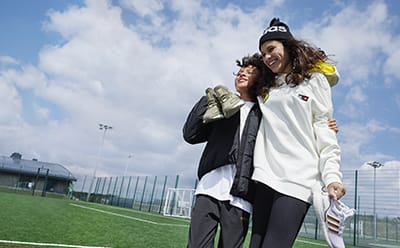 Boy and girl on a field wearing adidas products