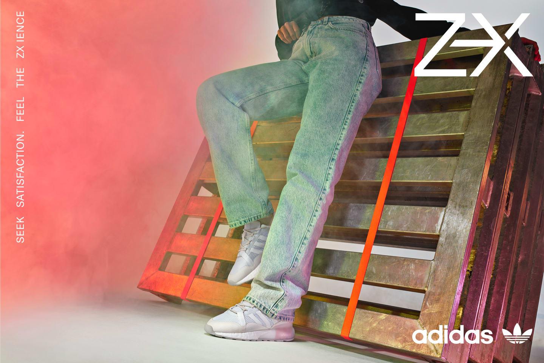 A standing model wears a women's ZX 2K BOOST PURE shoe.