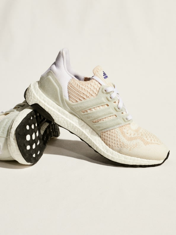 Pair of Ultraboosts with light background, one shoe on its side to show sole.