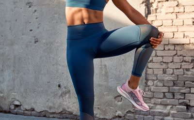 A close-up of a person lunging in adidas tights.