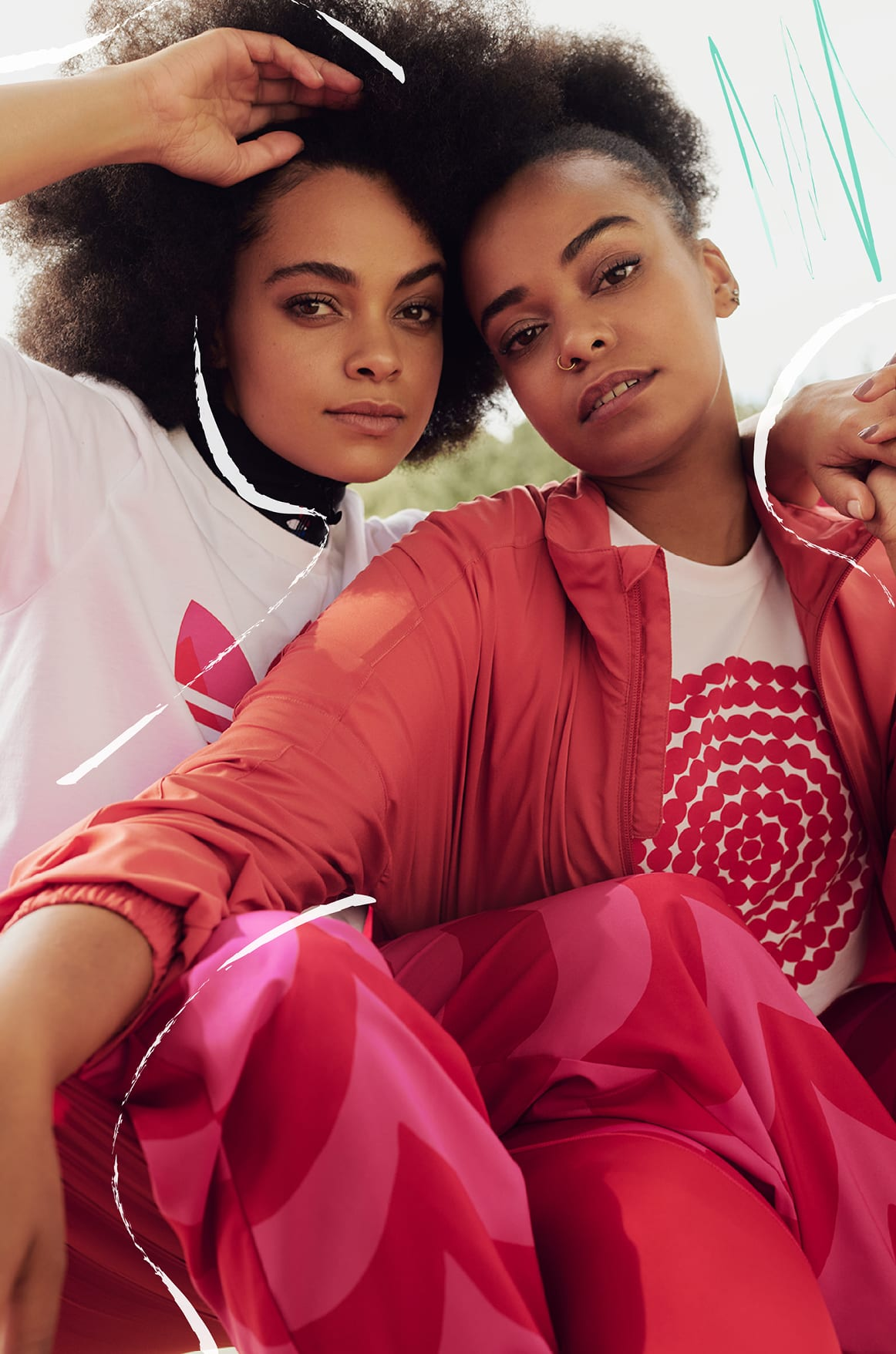 Two females, sat and looking straight at camera in pink and orange Marimekko outfits