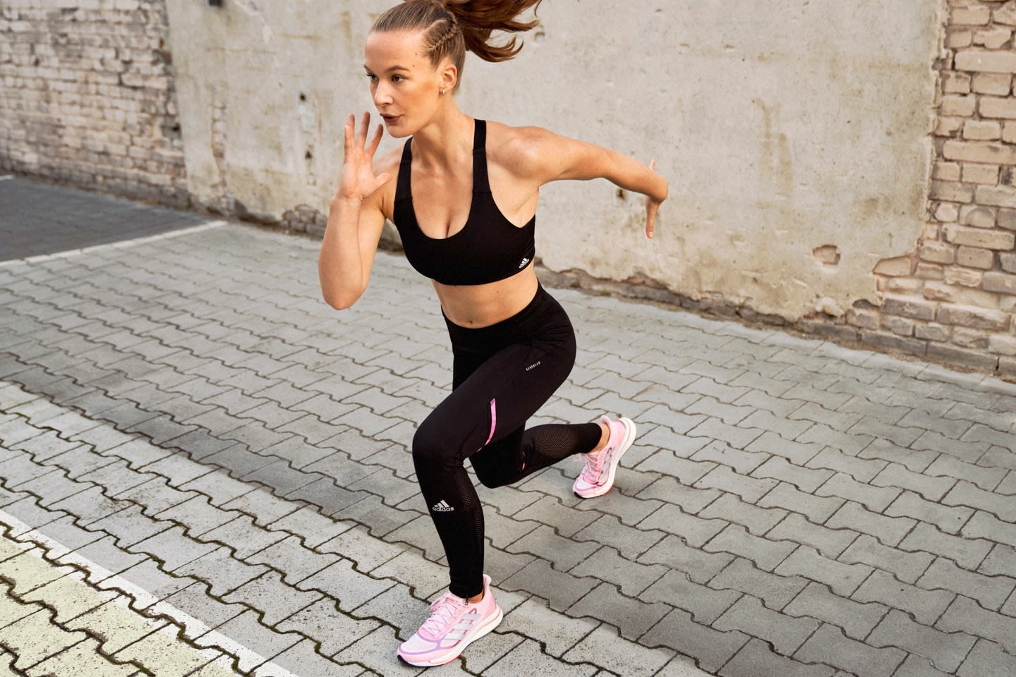 A woman wearing an adidas bra and tights holds a yoga pose in front of a concrete wall.