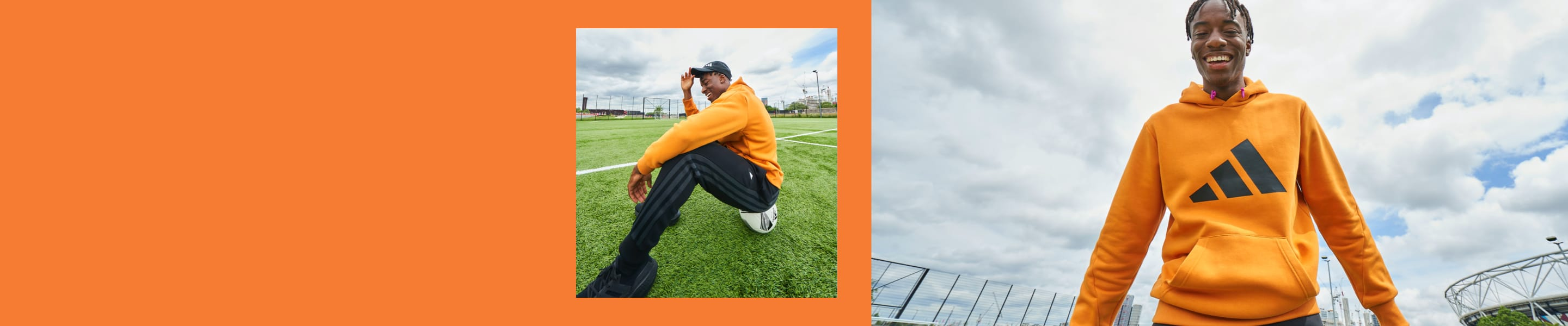 English footballer Noni Madueke looks up at the camera, smiling, as he stands on a football pitch in an orange adidas hoody.