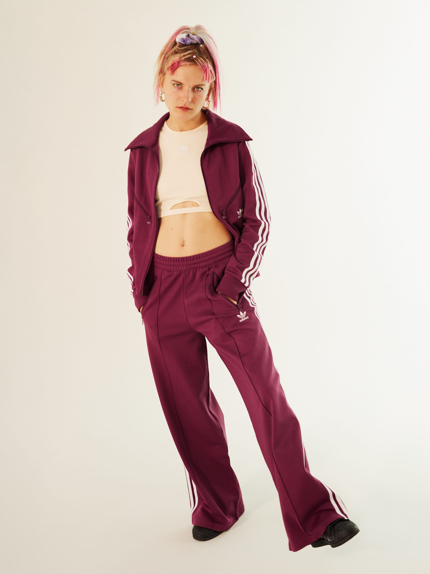 Stylish woman wearing a classic dark red adicolor tracksuit.