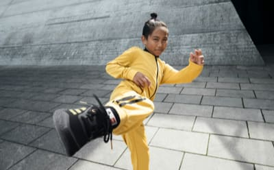 A model doing a karate kick wearing black shoes and yellow apparel from the adidas x LEGO® week collection.