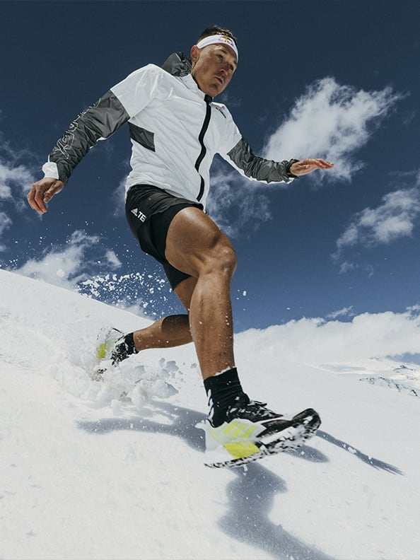 Athlete Dima wearing the Agravic Ultra running down snowy mountain trails