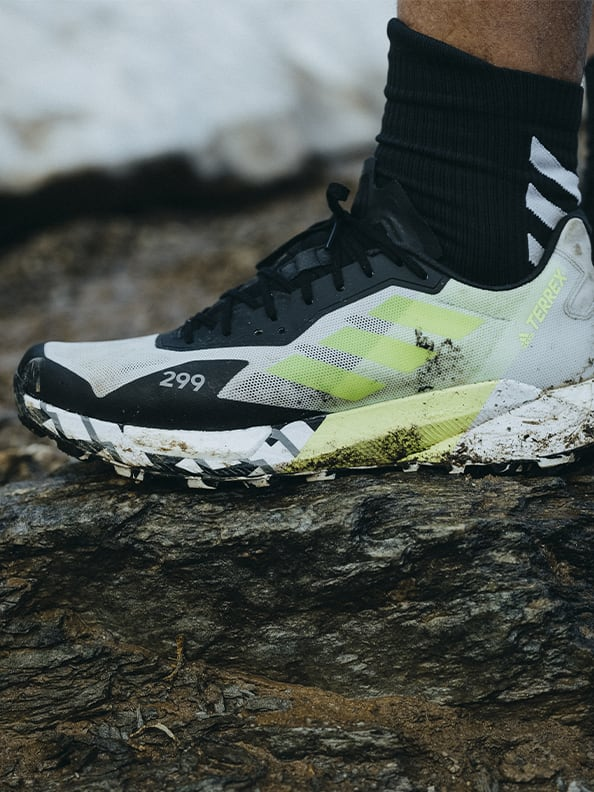 Athlete wearing the Agravic Ultra standing on muddy mountain trails