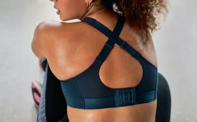 Primo piano della schiena di una donna che indossa un reggiseno sportivo con design incrociato sulla schiena.