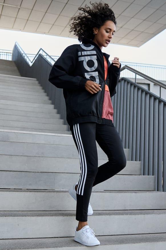 Una donna dal look casual che scende le scale indossando tight e giacca adidas.