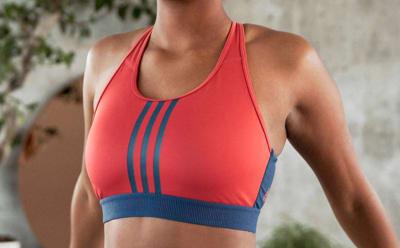 Een close-up van de borst van een vrouw die een rood met blauwe beha draagt.