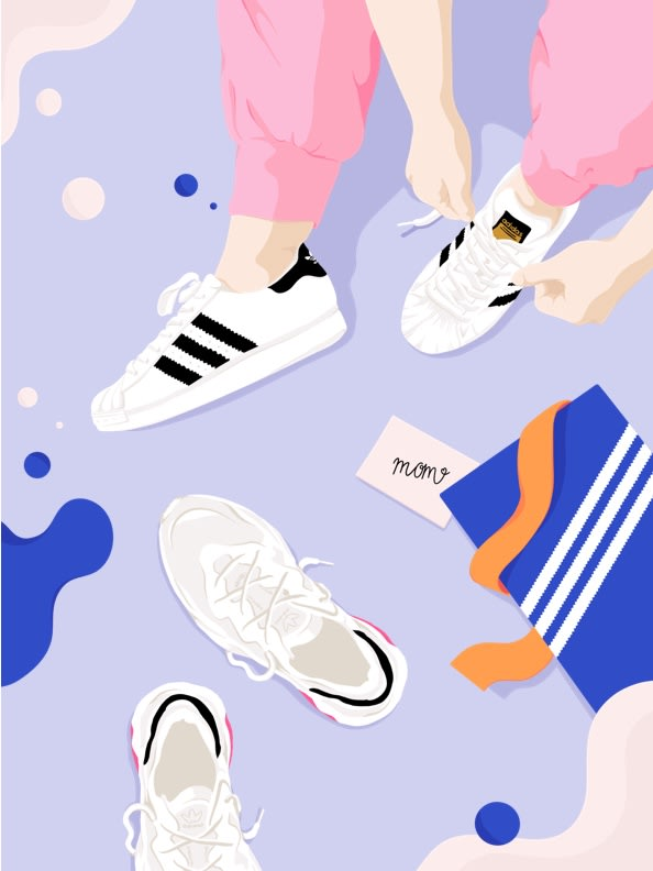 Top view of a moms feet as she puts on a new pair of Superstar shoes beside an open shoe box and a pair of UB21 sneakers.