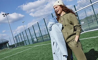Woman holding blue jacket in outdoor sports centre.