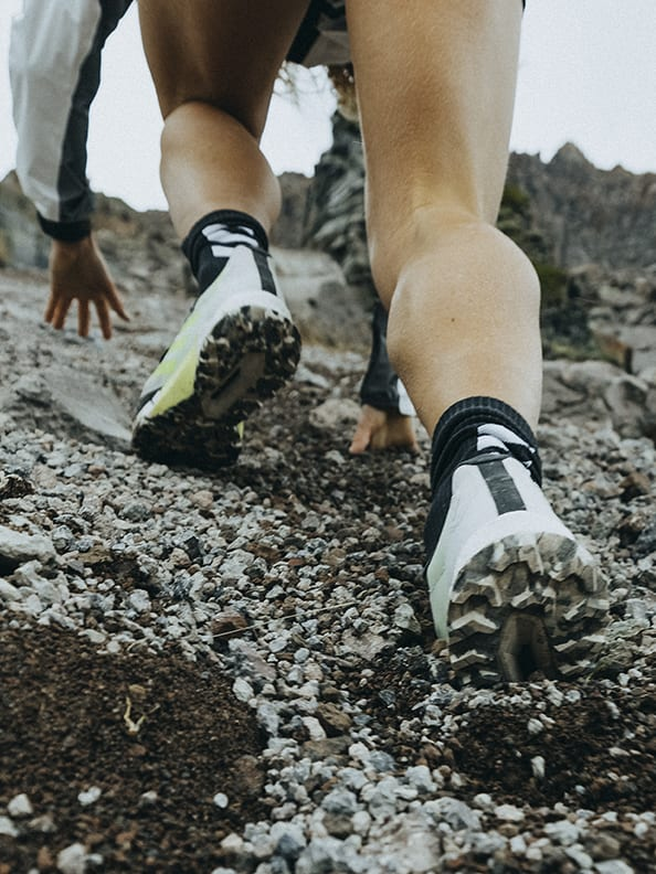 Athlete Ekaterina wearing the Agravic Ultra running up rocky mountain trails