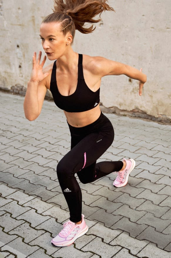 A woman wearing adidas bra and tights lunges as she trains outdoors.