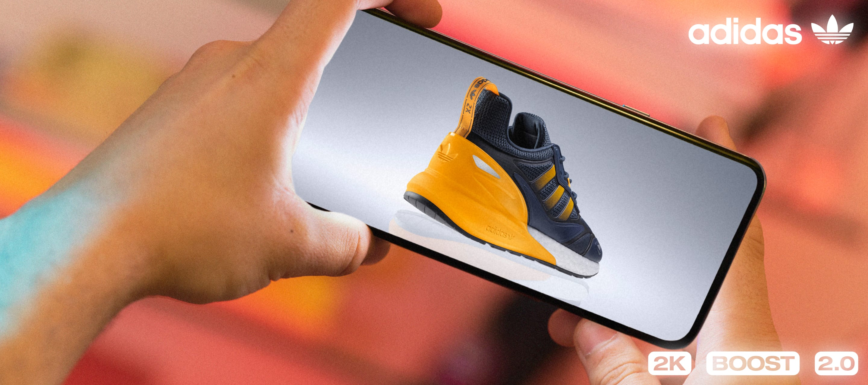 A model holds a cell phone that shows a back view of the ZX 2K Boost 2.0.