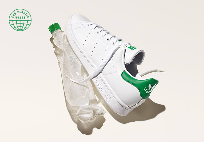 A Stan Smith shoe next to a crumpled water bottle on a white background.