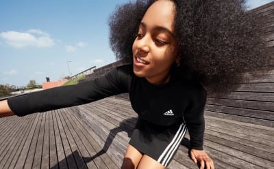 A child at an outdoor stadium wears black adidas clothing with three stripes.