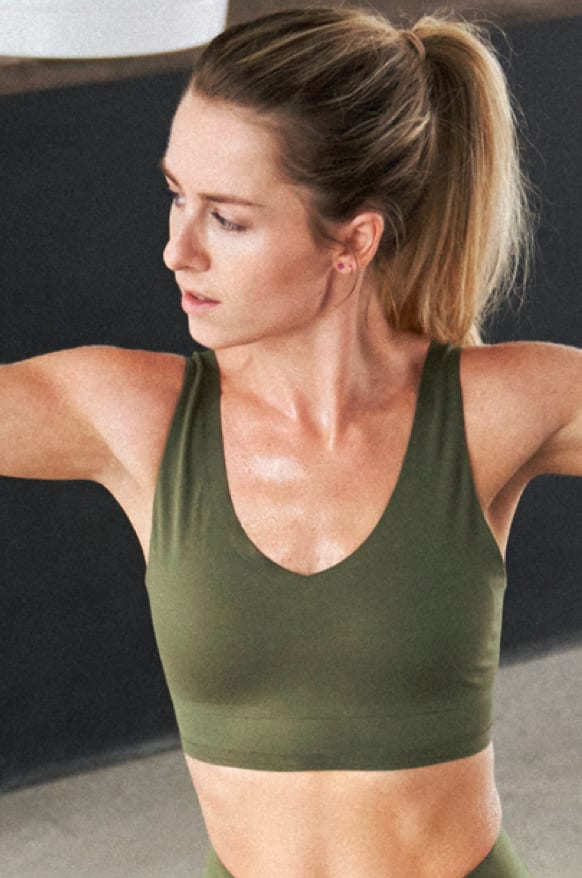 A woman in an olive bra holds a simple yoga pose.