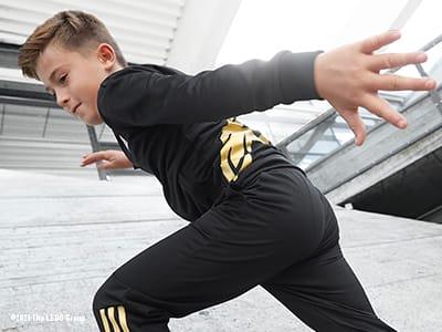 Kids posing, running and kicking in NINJAGO® outfits.